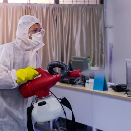man in PPE Kit Spraying Disinfectant